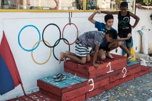 Children play on a podium erected in front of the Olympic rings.