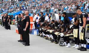 New Orleans Saints players stand and sit during the national anthem at Bank of America Stadium.