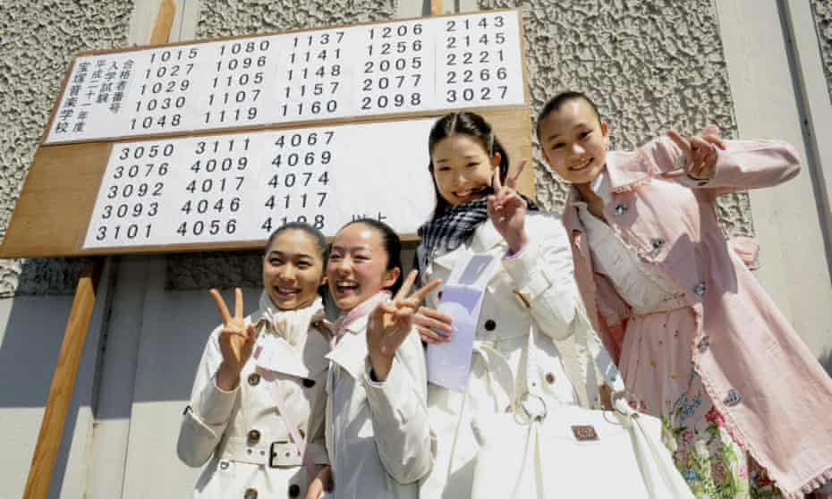 Four girls pose in front of a board showing that they are among 40 applicants who have passed this year's entrance exam for the noted Takarazuka Music School in Hyogo Prefecture.