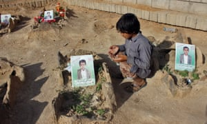 A Yemeni boy recites a prayer by the graves of pupils killed