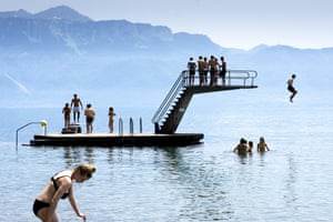 Children jump into the water of Lake Geneva to cool off.