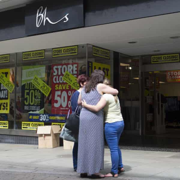 BHS workers hug outside a closing store in Newport, Wales.