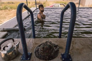 A Kurdish YPG soldier from the SDF bathes in the pool of a house used by soldiers