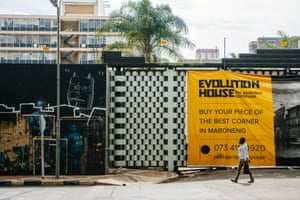 A pedestrian passes by a residential construction project in Maboneng.