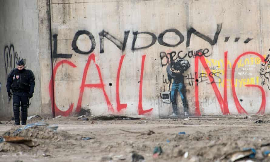 A French riot police officer near graffiti during the dismantling of part of the Calais refugee camp.