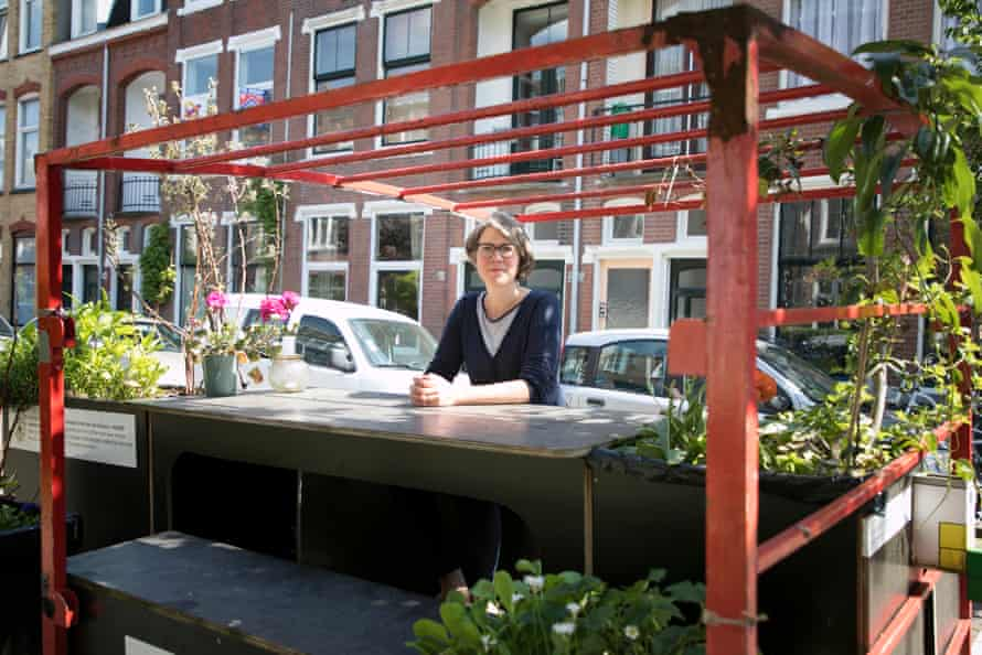 Eline Keus, an active member of de natuurlijke stad ('the natural city') in The Hague, sits at her flower-filled parking spot.