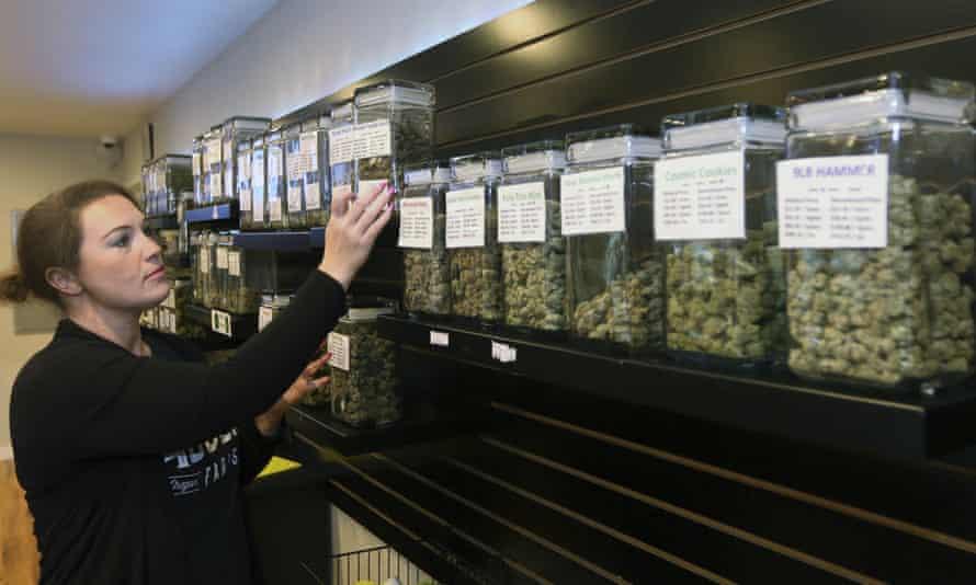 Diana Calvert, manager of the River City Retail marijuana dispensary in Merlin, Oregon, stocks shelves.