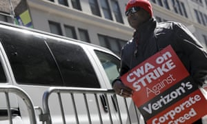 A member of the Communications Workers of America pickets in front of Verizon corporate offices during a 2016 strike in New York City.