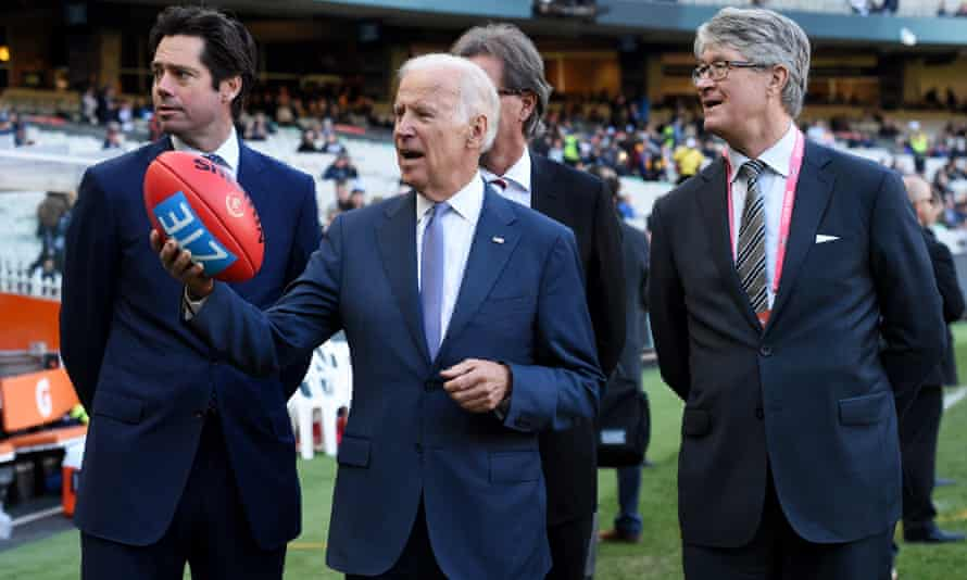 Joe Biden holds up an AFL football