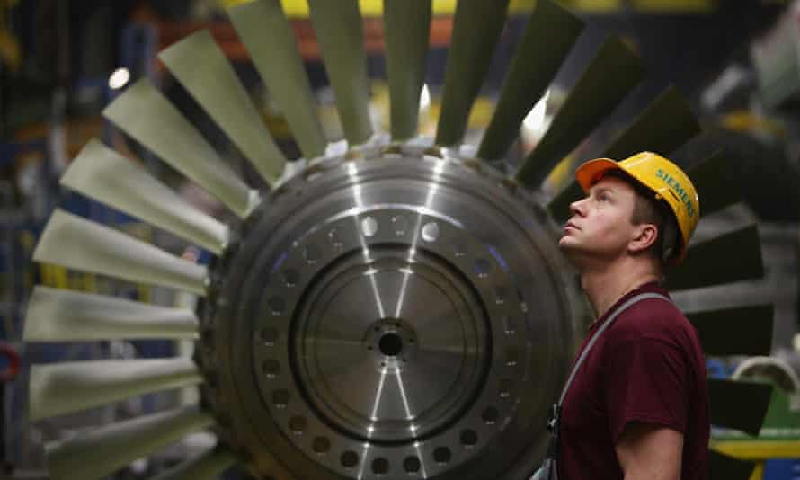 A worker watches as a heavy piece for a turbine moves above him while standing in front of a rotor assembly at the Siemens gas turbine factory on January 8, 2010 in Berlin, Germany.