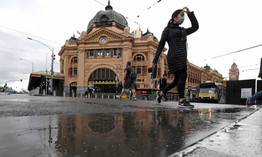 People wearing face masks walk across the road at Flinders Street Station in Melbourne