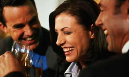 woman laughing with men in a bar