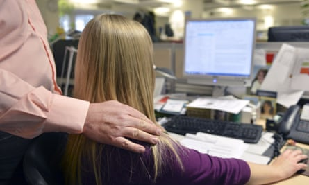 A female office worker receiving unwanted physical advances from a male co-worker