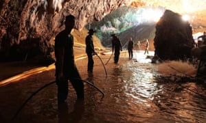 Thai rescue teams arrange a water pumping system at the entrance to a flooded cave on 7 July.