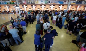 Thomas Cook passengers queue at check-in desks