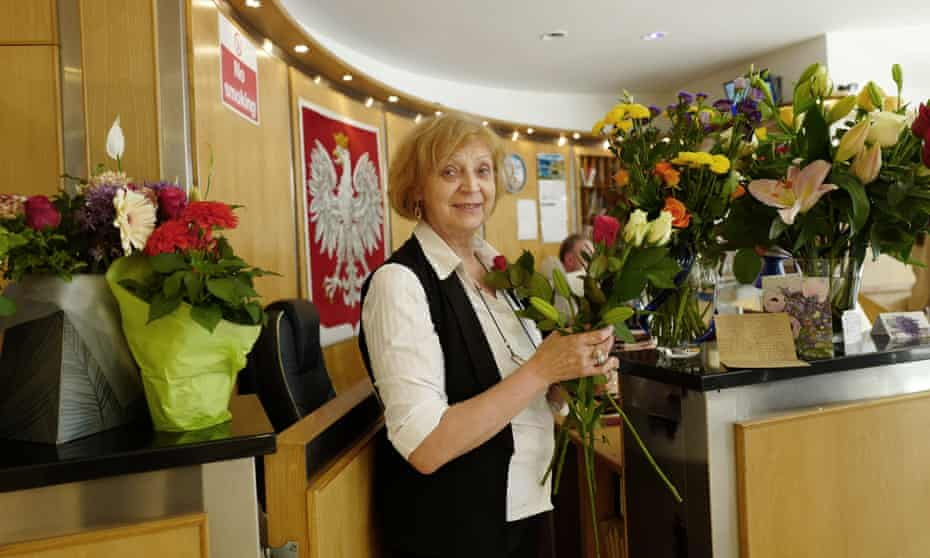Jadwiga Dee, receptionist at the The Polish Cultural Center in Hammersmith, with flowers donated in solidarity, following a racist grafitti attack.