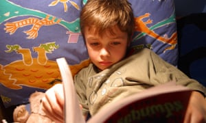 Young boy reading book in bed