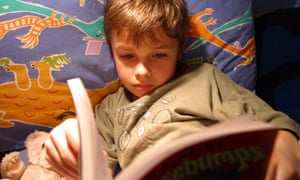 Young boy reading a book in bed at bedtime