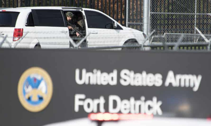A member of the Frederick police department special response team peers out of a minivan before the team entered Fort Detrick in a convoy of vans and sedans following a shooting in the Riverside Tech Park, near the Royal Farms on Monocacy Boulevard, Tuesday, 6 April 2021.