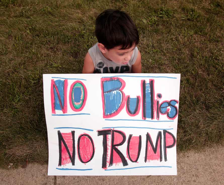 Stavros Metropoulos, 6, sits with a sign protesting an appearance by Donald Trump in Birch Run, Michigan.