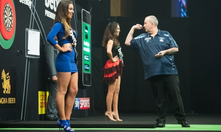 Darts player Phil Taylor warms up on stage with two walk-on girls.