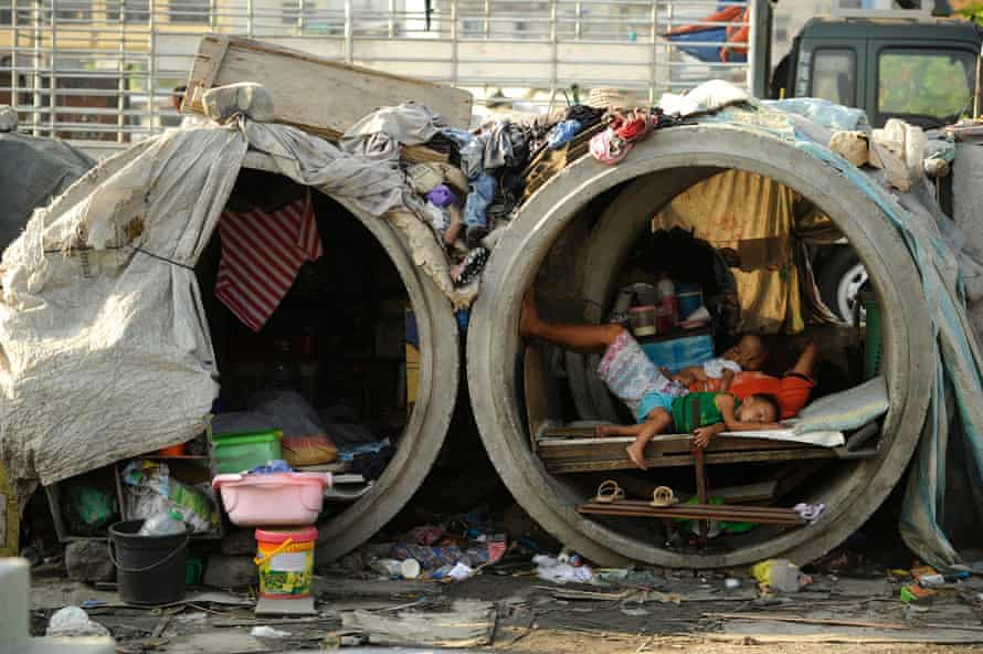 Families live in concrete pipes used as makeshift dwellings along a street in Manila. A quarter of the nation's 100 million people live in poverty.
