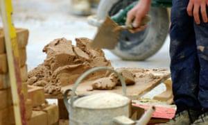 A bricklayer mixing mortar