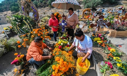 People decorate a relative's grave before the Day of the Dead at the Municipal Pantheon in Valle de Chalco, Mexico state, on Wednesday.