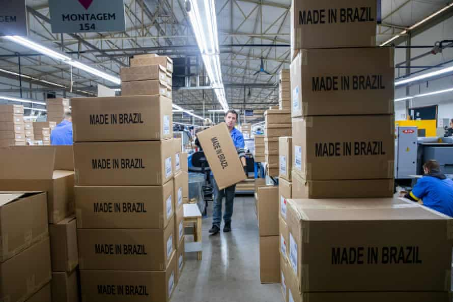 A man carries boxes of shoes labelled 'Made In Brazil'.