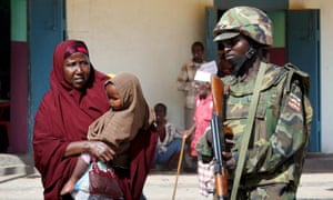 A Somali woman passes an African Union peacekeeper from Uganda.