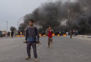 Children play on a street blocked with burning tyres, amid a general strike in the southern city of Basra, Iraq.