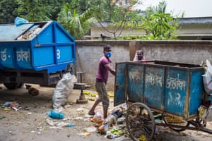 A masked refuse collector empties a rubbish cart