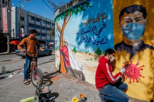 "Rafah, Gaza Strip An artist paints a mural reading ""By fighting the epidemic, we protect the human being and preserve the earth"" in the southern Gaza Strip"