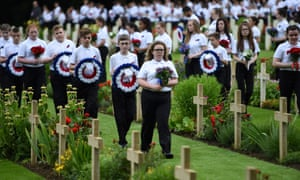 Young people holding flowers and wreaths take part in a memorial ceremony at Thiepval.