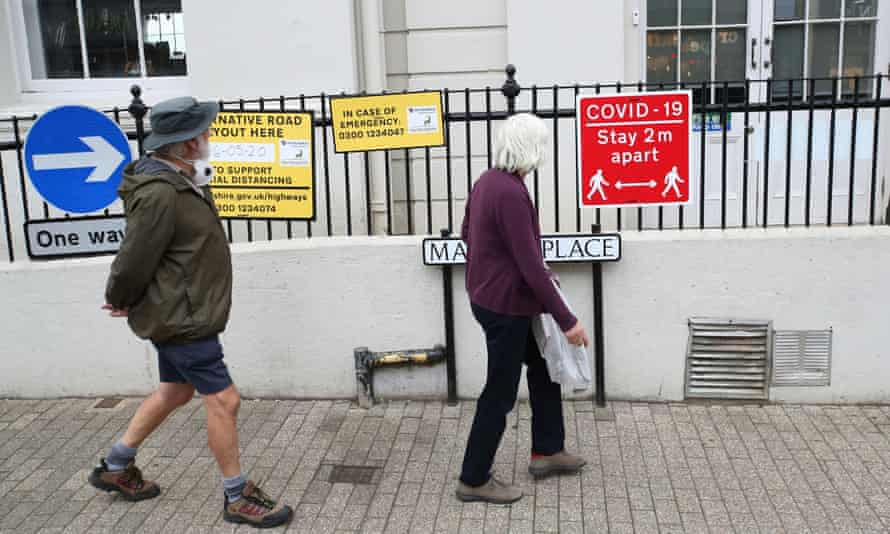 Older people in St Albans walking past a 2m distance sign