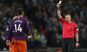 Manchester City's Aymeric Laporte is given a yellow card by Kevin Friend against Spurs at Wembley