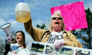 Protesters hold up jugs of discolored water outside the Farmers Market in Flint, marking the one year anniversary of the city switching from using Detroit water to Flint River water.