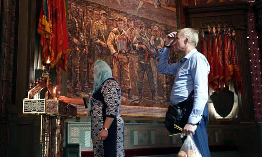 Russian Orthodox Christian light candles near a mosaic depicting more recent conflicts.