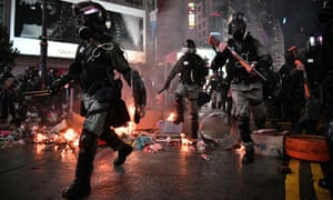 Police run past debris set alight by protesters in the Causeway Bay area of Hong Kong.