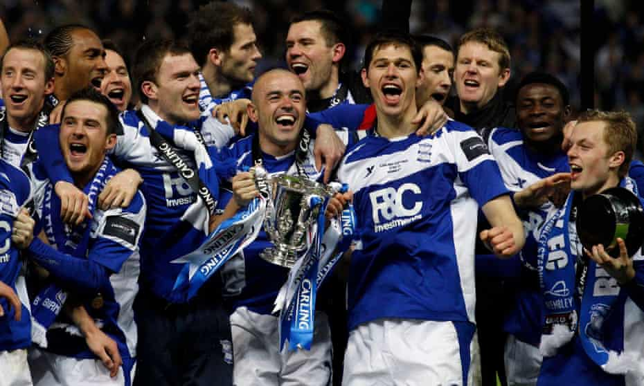 Stephen Carr holds the trophy aloft as he celebrates with team-mates after beating Arsenal.