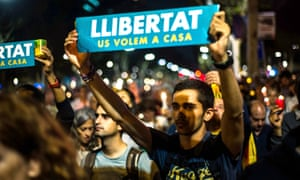 An independence campaigner holds a placard saying 'Freedom – we want you back home' at a rally in Barcelona