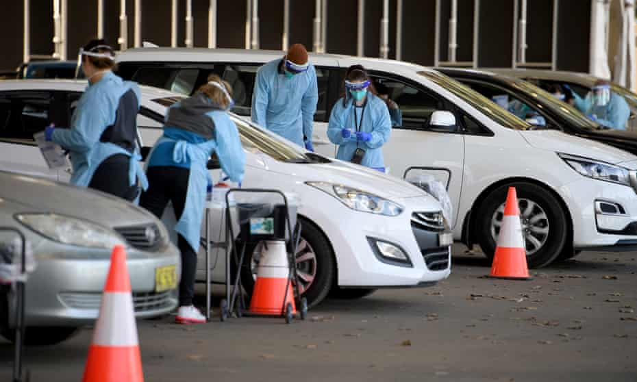 Health workers administer Covid tests at a drive-through testing clinic at Fairfield in Sydney