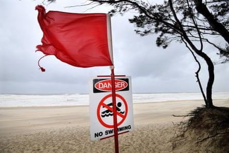 A red flag and a no swimming sign are seen at Southport beach on the Gold Coast on Sunday.