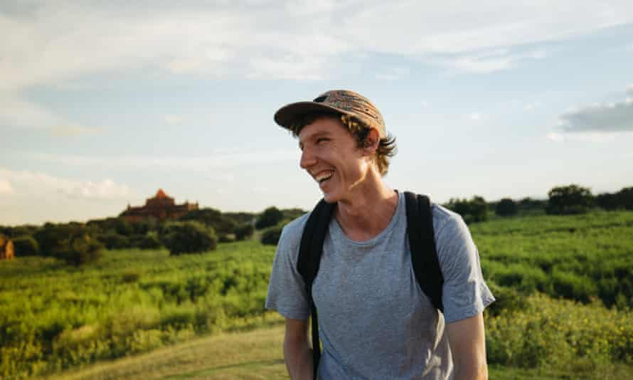 Western backpacker smiling outdoors with temple in the