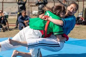 Meerim Momunova wrestles with her fellow Kyrgyz teammate Anara Ryskulova during a performance of a traditional Alysh wrestling