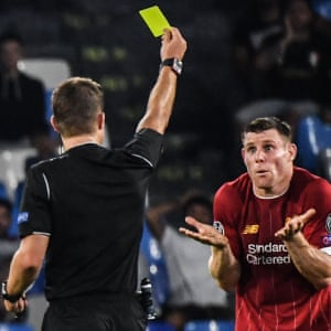Referee Felix Brych (left) gives a yellow card to Liverpool's James Milner.