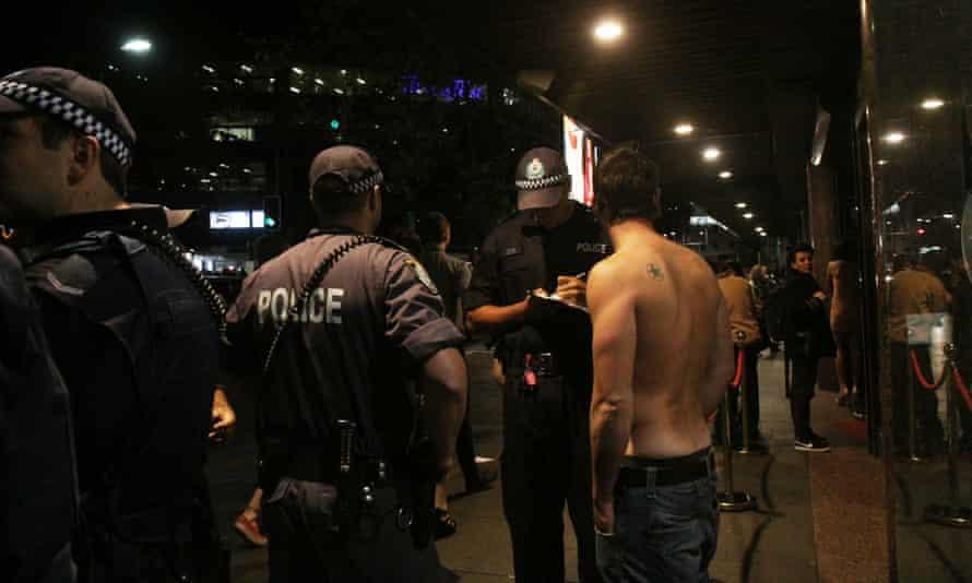 Police officers speak to a man in Kings Cross
