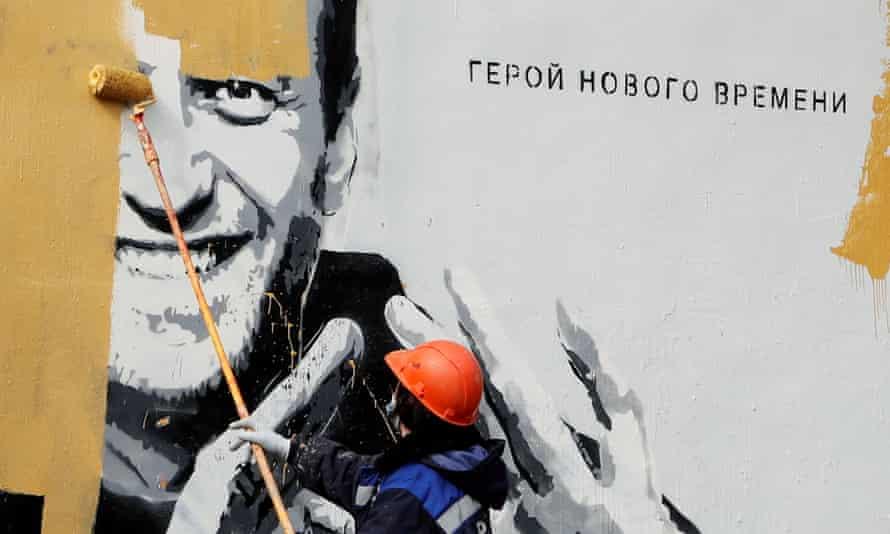 Un muncitor pictează peste o pictură murală care îl înfățișează pe Alexei Navalny în Saint Petersburg în aprilie