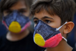 Children wear masks during Sydney's Invasion Day rally.