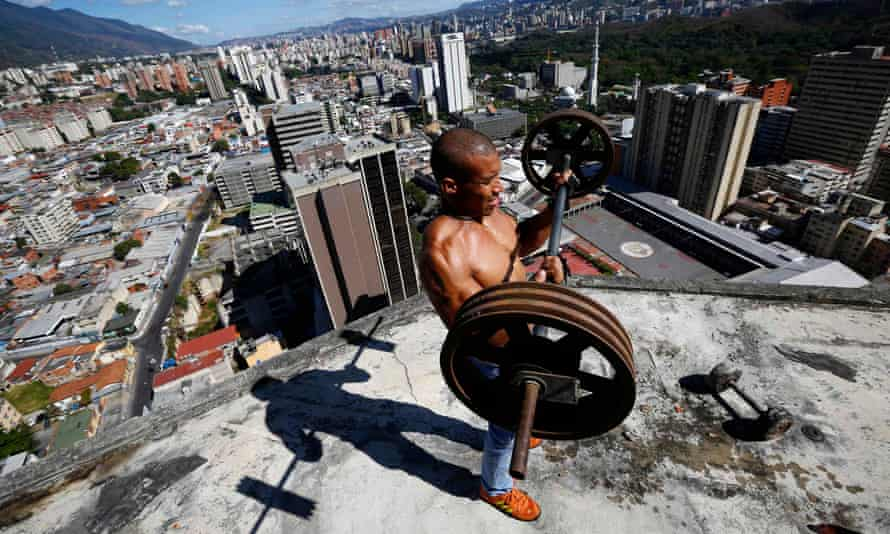 A man lifts weights on the balcony of the 28th floor of the abandoned 'Tower of David' skyscraper in Caracas, Venezuela.